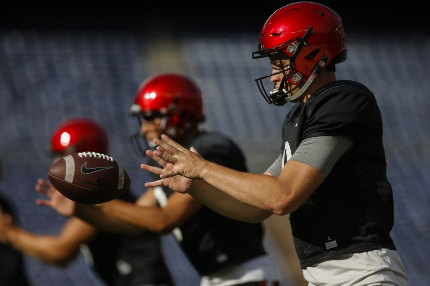 San Diego State quarterback Ryan Agnew takes a snap alongside backup quarterbacks Carson Baker and Jordon Brookshire during warmups before last week's Fan Fest scrimmage at SDCCU Stadium.