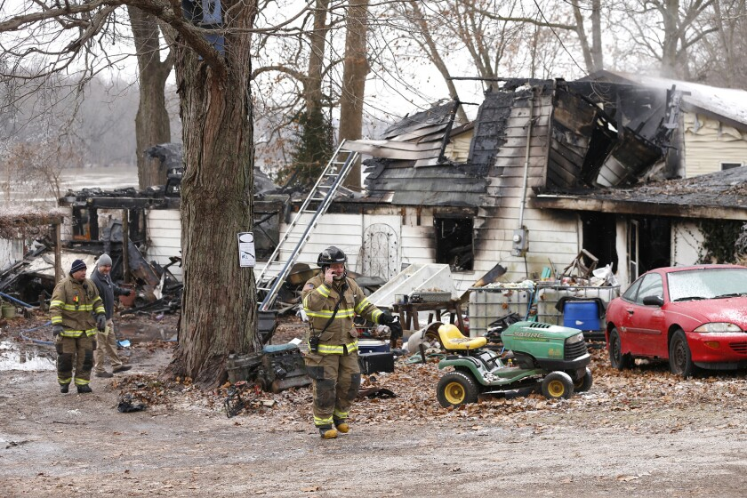 Firefighters remain on the scene following an early morning house fire on Wednesday, Nov. 28, 2018 in Logansport, Indiana.