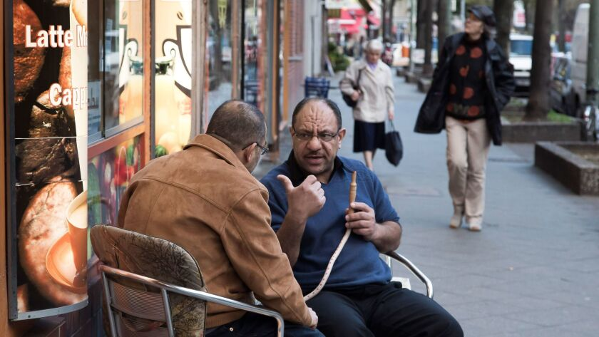 El Mohamed, right, smokes a hookah pipe as he talks with native Palestinian Yaser A Rabah in front of a bar at Sonnenallee in the Neukoelln district of Berlin.