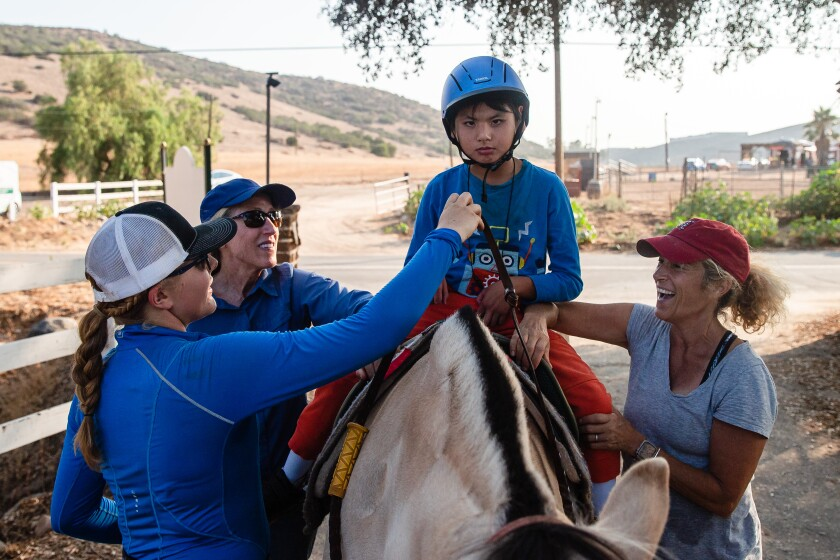 Eddie Quach, 12, takes a therapeutic riding lesson Aug. 17 at Ride Above Disability Therapeutic Riding Center in Poway.