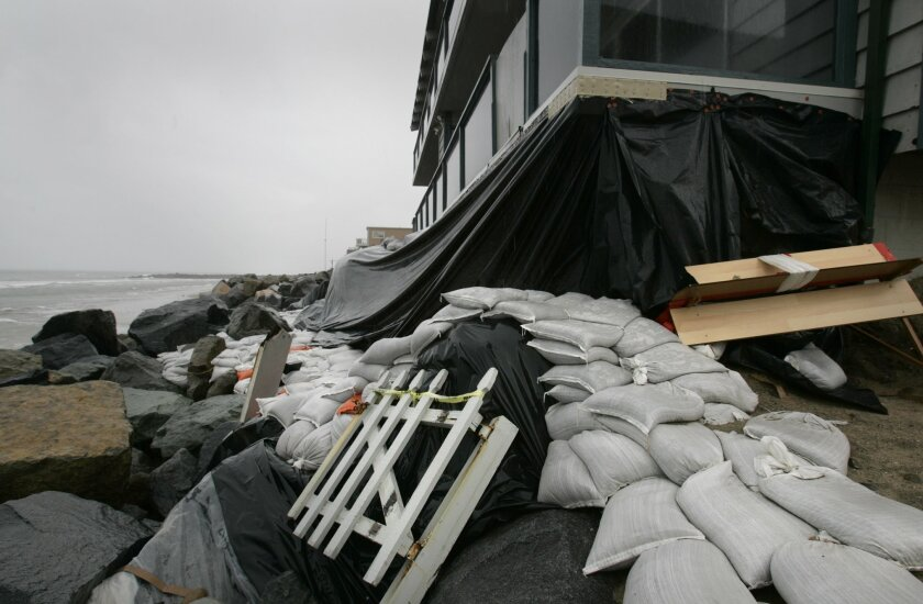 Residents of a condominium complex have placed sandbags to protect against the high tides and big waves that have removed much of the sand that was a barrier between their property and the ocean. Some residents blame a nearby development for the problem.
