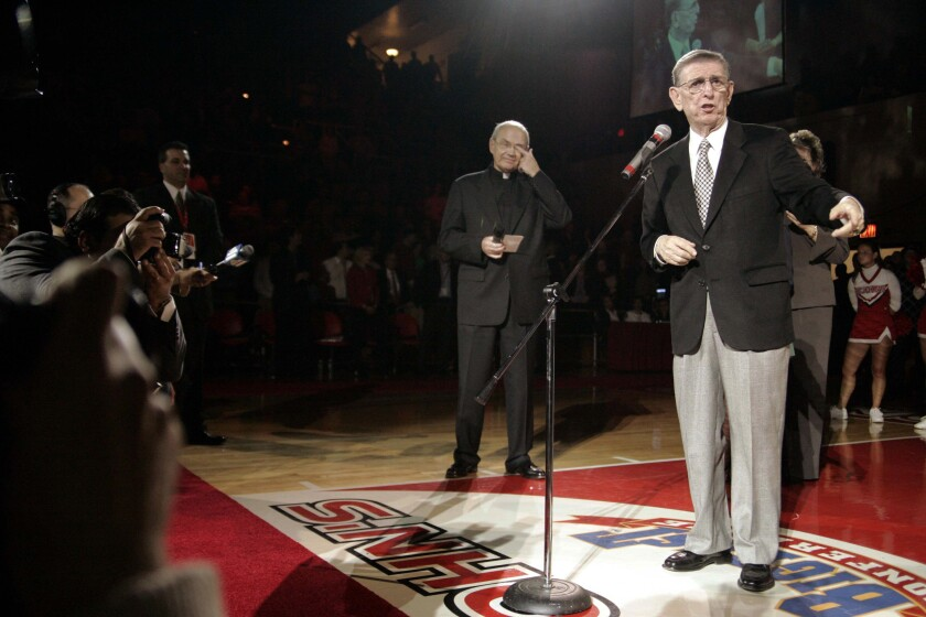 FILE - In this Nov. 23, 2004, file photo, former St. John's basketball coach Lou Carnesecca, right, addresses fans at St John's in New York at a ceremony that was to rename the court for the longtime former coach. Looking on is Donald J Harrington, then-president of the university. St. John's plans to unveil a statue of Hall of Fame coach Carnesecca this fall in the on-campus arena that bears his name. (AP Photo/Ed Betz, File)