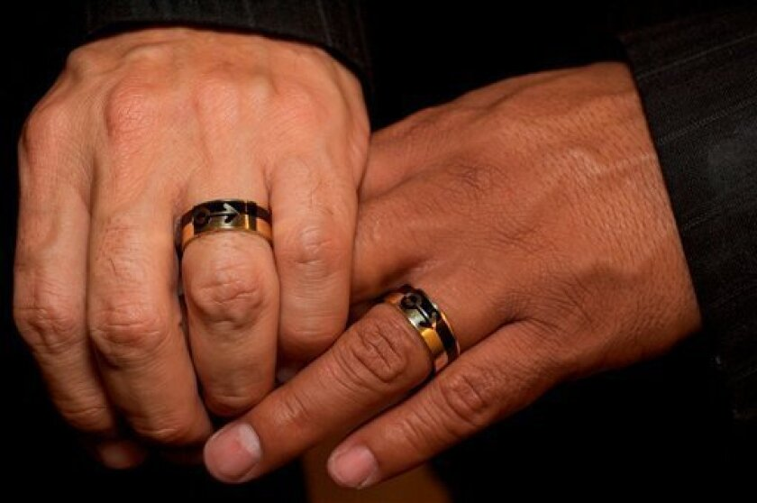"In this file photo from June 17, 2008, Eric Manriquez, left, and Juan Rivera hold their gold wedding rings together as they get married in East Los Angeles. On Wednesday, Dec. 10, supporters of same-sex marriage across the country are being encouraged to stay home and call in ""gay"" to work to protest the passage of Proposition 8. (AP Photo/Damian Dovarganes, File)"