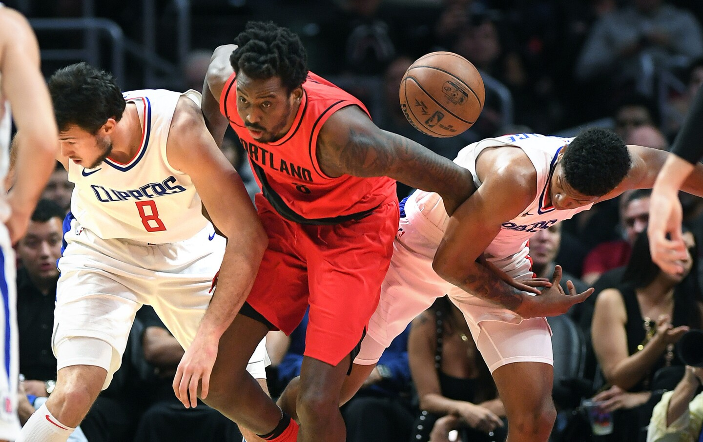 Clippers Danilo Gallinari, left, and Tyrone Wallace battle for a loose ball with Trail Blazers' Al-Farouq Aminu in the 4th quarter.