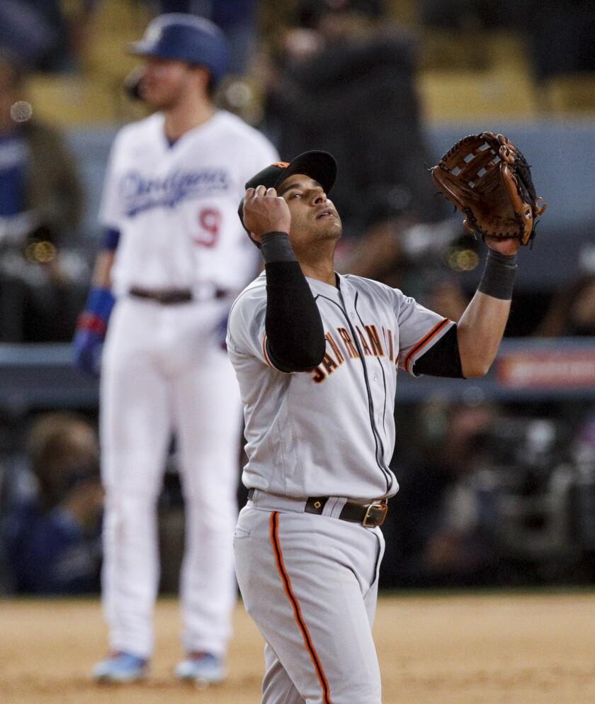 Giants second baseman Donovan Solano celebrates as Dodgers hitter Gavin Lux stands stunned.