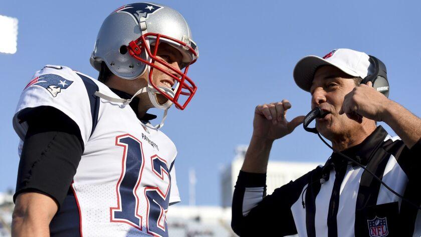 New England Patriots quarterback Tom Brady, left, talks to referee Gene Steratore (114) prior to an