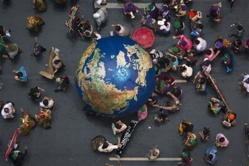 "Activists push an inflatable globe during a ""Global March"" as part of the People's Summit for Social and Environmental Justice in Defense of the Commons, a parallel event during the UN Conference on Sustainable Development, or Rio+20, in Rio de Janeiro, Brazil, Wednesday, June 20, 2012. (AP Photo/F"