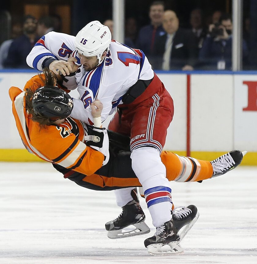 New York Rangers left wing Tanner Glass (15) knocks Philadelphia Flyers center Ryan White (25) to the ice as the two fight during the first period of an NHL hockey game, Sunday, Feb. 14, 2016, in New York. (AP Photo/Julie Jacobson)