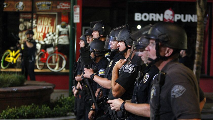 """Police confront rioters in Huntington Beach after the U.S. Open of Surfing finals in 2013 — the only riots to take place in the area recently, contrary to President Trump's claims of riots against California's """"sanctuary"""" law."""