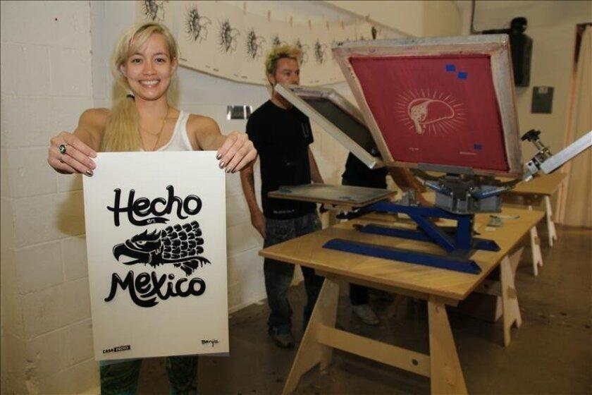 """Fotografía del 25 de mayo de 2013 de Peising Yang Lazo (i) mostrando un afiche de estampado en serigrafía que aprendió a crear en un taller impartido por Ducky Harris (d), en la """"Casa Indio"""" de Los Ángeles, California. EFE"""