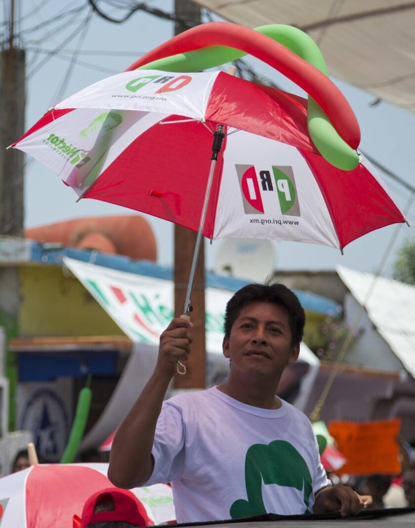 En esta imagen del 18 de mayo de 2016, un seguidor se protege del sol con un paraguas del Partido Revolucionario Institucional (PRI) mientras espera al candidato a gobernador de Veracruz Héctor Yunes Landa durante un acto de campaña en Cosoleacaque, en el estado de Veracruz, México. Los sondeos señalan que el PRI tiene una posibilidad de volver a ganar en Veracruz y en la mayoría de otros 11 estados que celebran elecciones regionales el domingo 5 de junio, victorias que podrían allanar su camino a conservar la presidencia del país dentro de dos años. (AP Foto/Eduardo Verdugo)