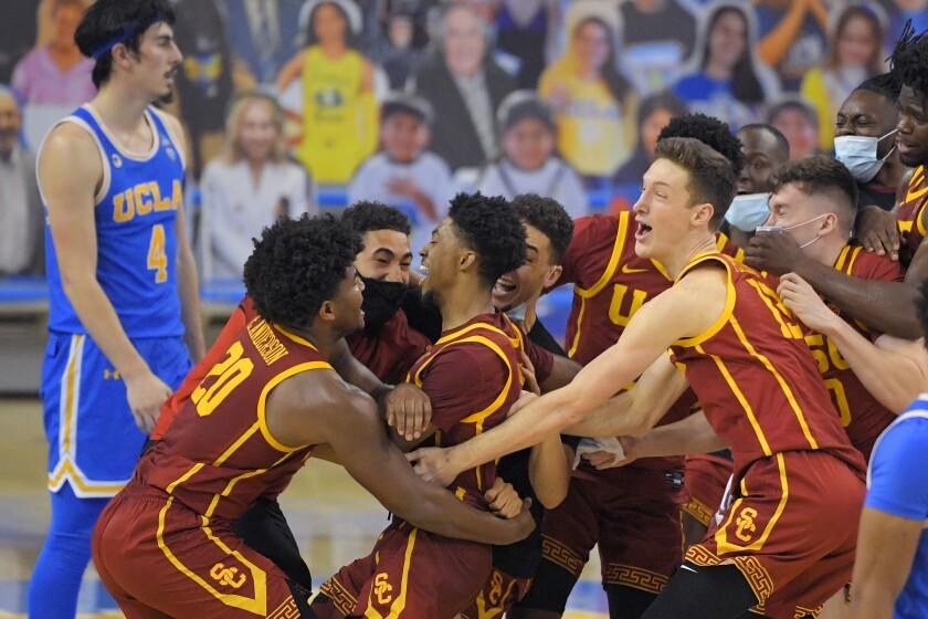 USC's Tahj Eaddy celebrates with teammates as UCLA guard Jaime Jaquez Jr. walks off the court.