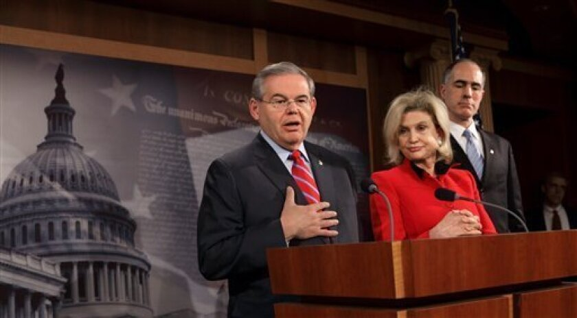 From left, Sen. Robert Menendez, D-N.J., Rep. Carolyn Maloney, D-N.Y., and Sen. Robert Casey, D-Pa. meet reporters on Capitol Hill in Washington, Friday, Feb. 6, 2009, to discuss efforts by Senate Democrats to pass the economic stimulus bill in the face of strong GOP opposition. (AP Photo/J. Scott Applewhite)