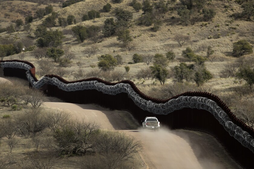 A Customs and Border Protection agent patrolling the U.S. side of a razor-wire-covered border wall east of Nogales, Ariz.