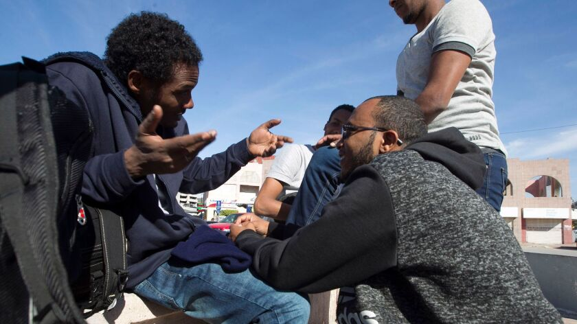 Mesfin Tesfaldet, 33, left, of Eritrea talks with other asylum seekers in a commercial plaza near the pedestrian crossing.
