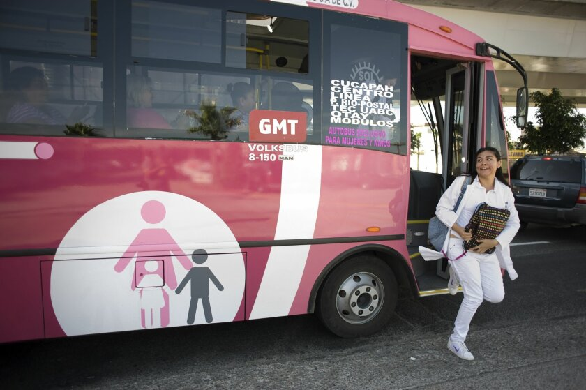 Glenda Hernández, a 20-year-old medical student, gets off a bus near her house in Tijuana's Mesa de Otay.