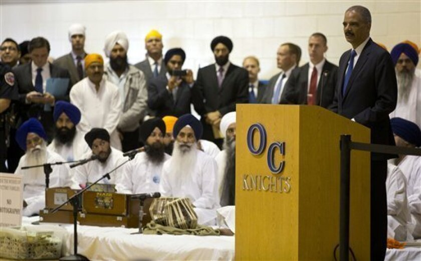 Attorney General Eric Holder speaks at the funeral and memorial service for the six victims of the Sikh temple of Wisconsin mass shooting in Oak Creek, Wis., Friday, Aug. 10, 2012. The public service was held in the Oak Creek High School. Three other people were wounded in the shooting last Sunday at the temple. Wade Michael Page, 40, killed five men and one woman, and injured two other men. Authorities say Page then ambushed the first police officer who responded, shooting him nine times and leaving him in critical condition. A second officer then shot Page in the stomach, and Page took his own life with a shot to the head. (AP Photo/Jeffrey Phelps)