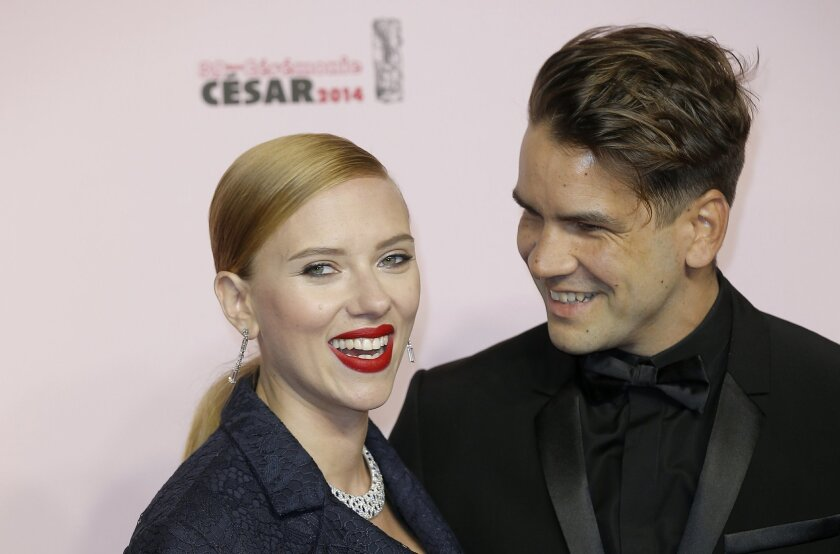 U.S. actress Scarlett Johansson, left, and her partner Romain Dauriac arrive at the 39th French Cesar Awards Ceremony, in Paris, Friday, Feb. 28, 2014. This annual ceremony is presented by the French Academy of Cinema Arts and Techniques. (AP Photo/Lionel Cironneau)