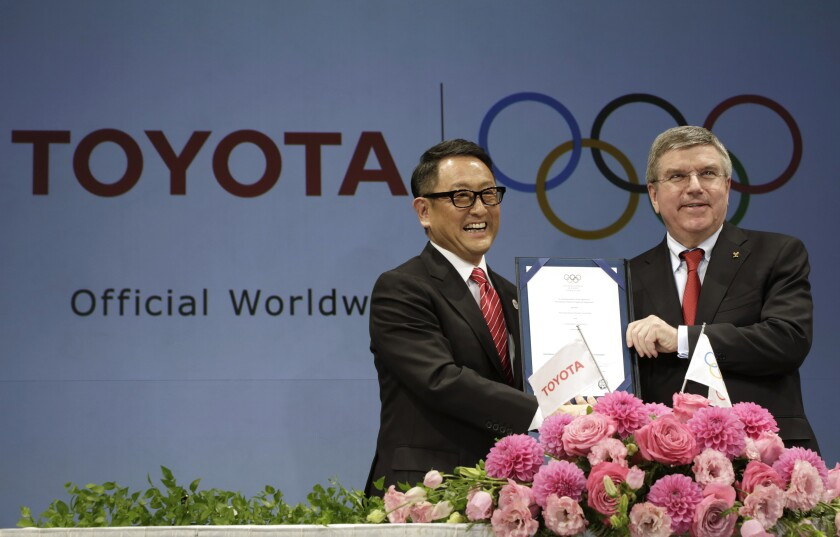 Toyota CEO and International Olympic Committee chief holding signed agreement