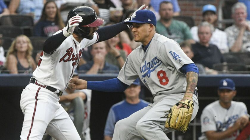 Los Angeles Dodgers shortstop Manny Machado (8) tags out Atlanta Braves' Nick Markakis in a rundown along the third base line during the second inning of a baseball game Friday, July 27, 2018, in Atlanta.