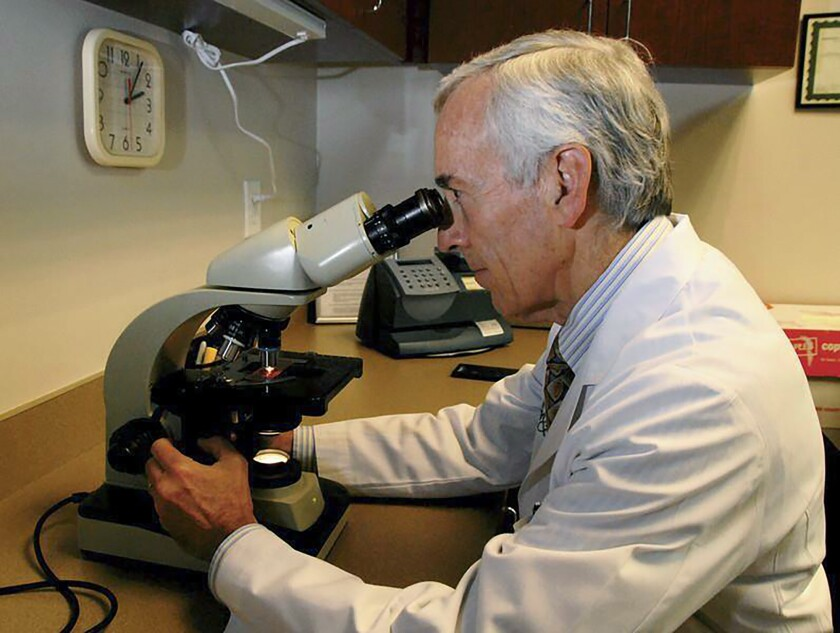 In this undated photo provided by Atlanta Allergy & Asthma, Dr. Stanley Fineman looks through a microscope at Atlanta Allergy & Asthma Center in Atlanta to examine the pollen. When Fineman started 40 years ago as an allergist in Atlanta, he told patients they should start taking their medications and prepare for the onslaught of pollen season around St. Patrick's Day. Now he tells them to start around St. Valentine's Day. (Robin B. Panethere /Atlanta Allergy & Asthma via AP)