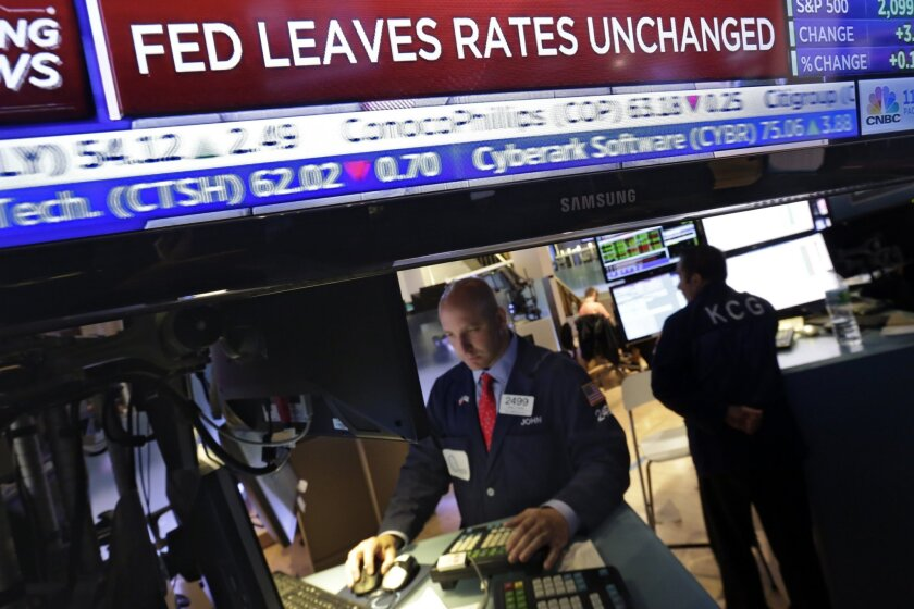 A television screen at the trading post of specialist John Parisi, left, on the floor of the New York Stock Exchange, shows the decision of the Federal Reserve, Wednesday, June 17, 2015. The U.S. economy has strengthened since a slump early this year, the Federal Reserve said Wednesday, but it wants to see further gains in the job market and higher inflation before raising interest rates from record lows. (AP Photo/Richard Drew)