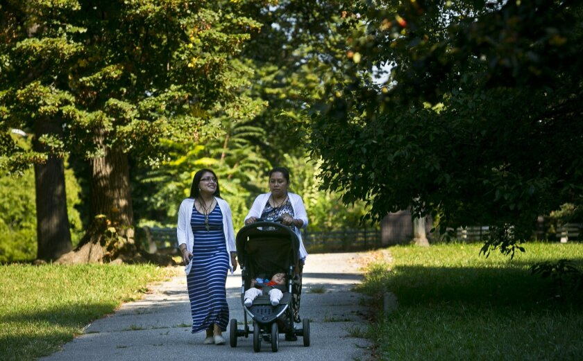 """Suleyma Cuellar, 20, left, walks with her mother Luisa Bravo, 40, and baby brother Francisco in Central Park, Friday Sept. 18, 2015, in New York. They are among 80,000 ticket holders who will have to go through heavy security and wait around for hour to see Pope Francis pass through Central Park. For ticket-holders like Cuellar and her mother, it's all worth it because """"it's like seeing Jesus walk by."""" (AP Photo/Bebeto Matthews)"""