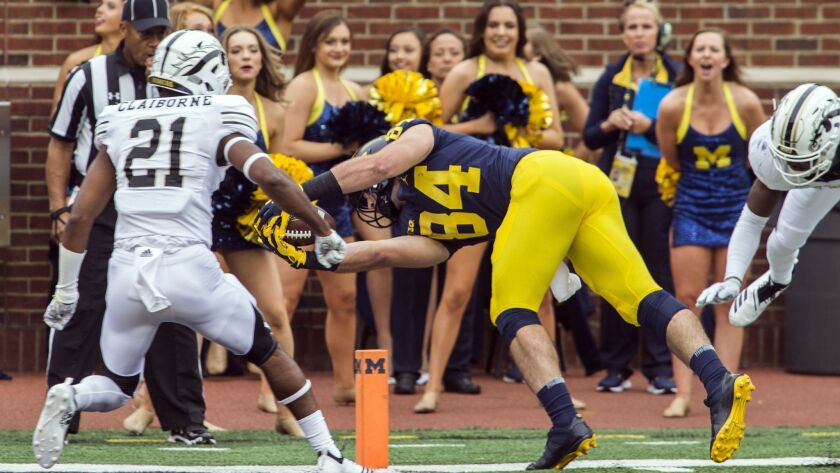 Michigan tight end Sean McKeon (84) dives for a 17-yard touchdown, defended by Western Michigan defe