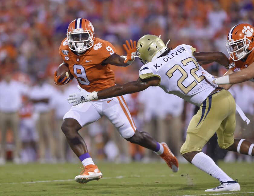 Clemson's Travis Etienne, left, fends off Georgia Tech's Kaleb Oliver to rush for a first down during the Tigers' season-opening win Thursday.
