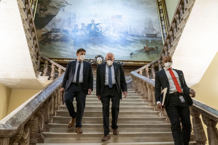 Sen. Bernie Sanders and others walking down a broad staircase at the Capitol