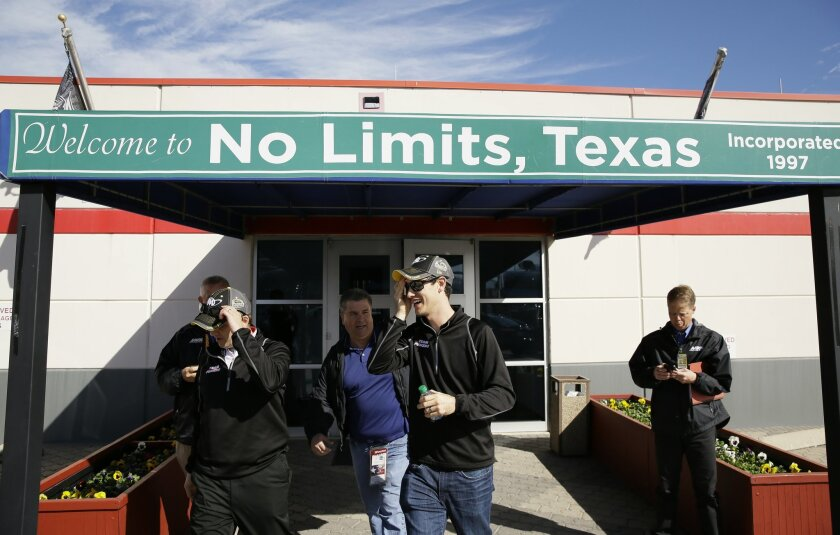 Joey Logano, center, heads to the garage before the start of NSACAR Sprint Cup auto race practice at Texas Motor Speedway Friday, Nov. 6, 2015, in  Fort Worth, Texas. (AP Photo/LM Otero)