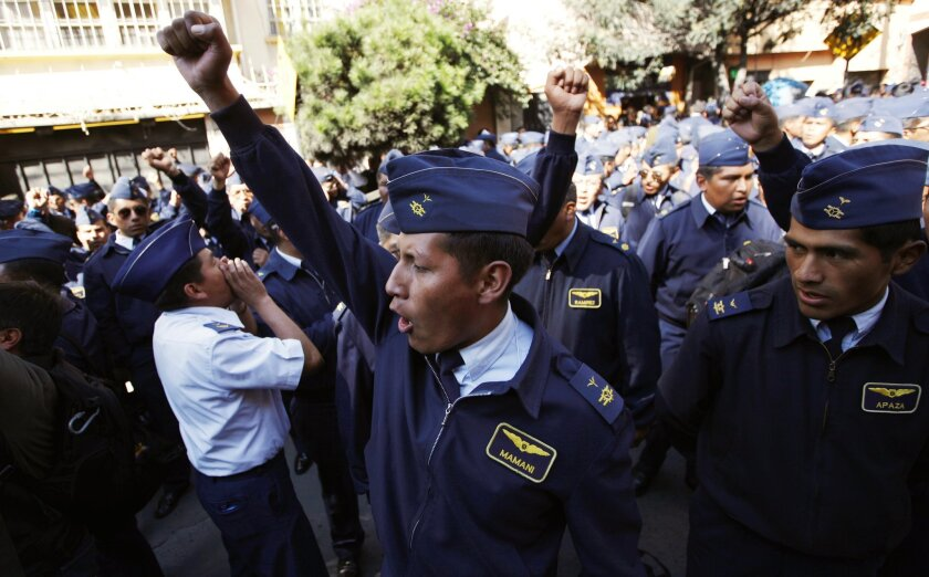 Members of the Air Force shout slogans as they protest in La Paz, Bolivia, Tuesday, April 22, 2014. Hundreds of low ranking soldiers from Bolivia's Armed Forces marched against the military high command's dismissal of four of its leaders who defended their call for more career opportunities. Soldiers who study three years to be sergeants and then warrant officers want the opportunity to rise in rank, according to Felix Jhonny Gil, president of the National Association of Warrant Officers and Sergeants. The soldiers' wives started a hunger strike in solidarity. (AP Photo/Juan Karita)