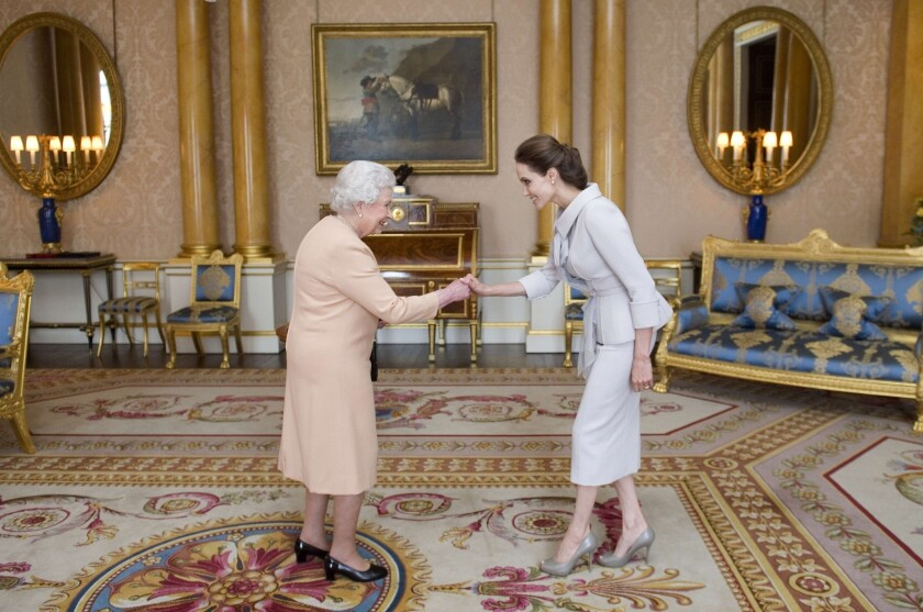 Angelina Jolie is presented with the Insignia of an Honorary Dame Grand Cross of the Most Distinguished Order of St. Michael and St. George by Queen Elizabeth II in the 1844 Room at Buckingham Palace on Oct. 10
