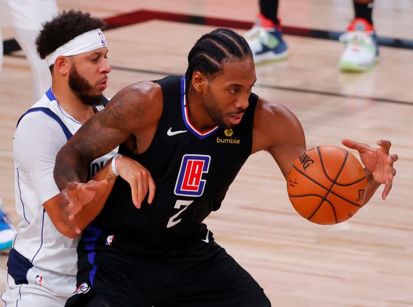 Clippers star Kawhi Leonard works against Dallas Mavericks guard Seth Curry.