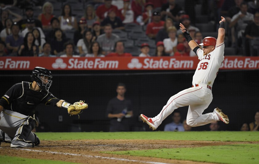 Angels' Kole Calhoun, right, slides before being tagged out by Pittsburgh Pirates catcher Jacob Stallings while trying to score on a ball hit by Matt Thaiss during the fifth inning on Tuesday at Angel Stadium.