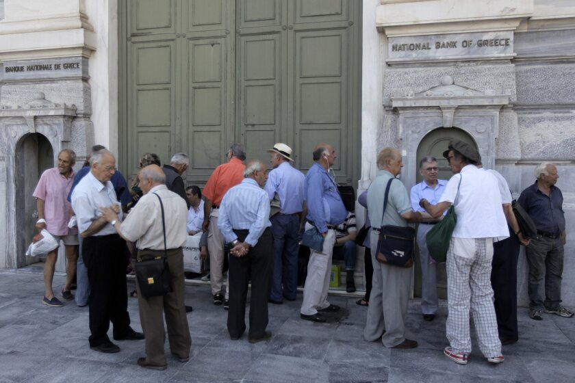 People wait outside a bank in Athens. The impact of Greece's financial crisis has yet to lead to many international trip cancellations, according to travel agents.
