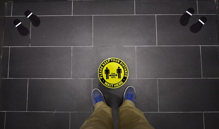Foot markings and a coronavirus social distance reminder are seen on the floor of an elevator in office building.