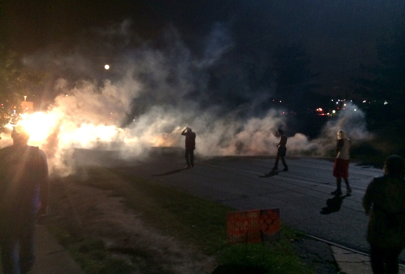In Ferguson, Mo., on Aug. 11, demonstrators scatter after facing tear gas on a hill.