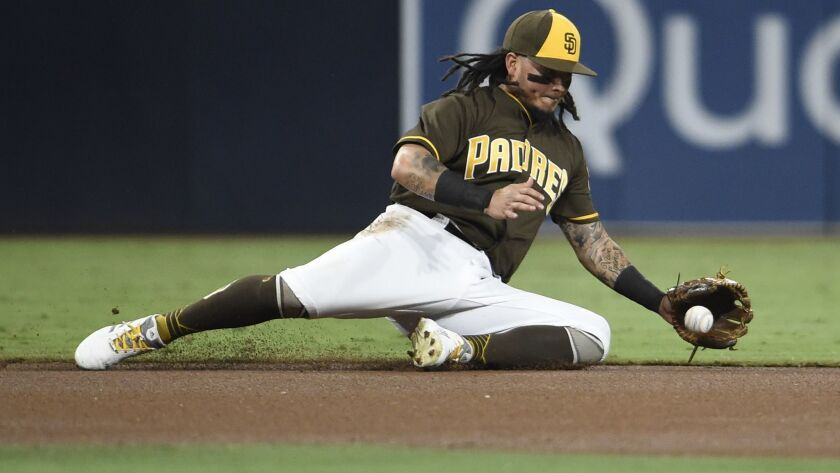 The Padres' Freddy Galvis #13 of the San Diego Padres makes a diving stop on a single hit by Arizona's Ketel Marte during the first inning of a baseball game at Petco Park on September 28, 2018 in San Diego, California.