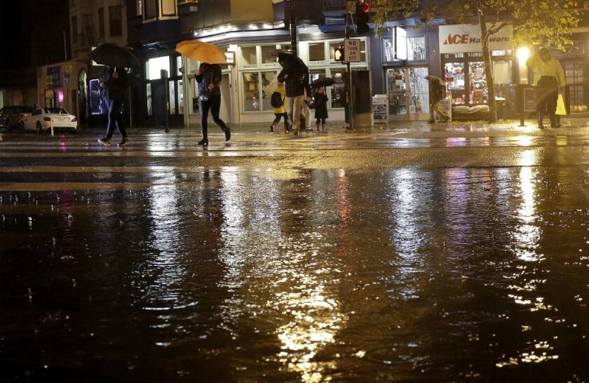 Both Southern and Northern California have been hit with a series of powerful rainstorms the past two months. Above, pedestrians walk by a flooded intersection in San Francisco in December.