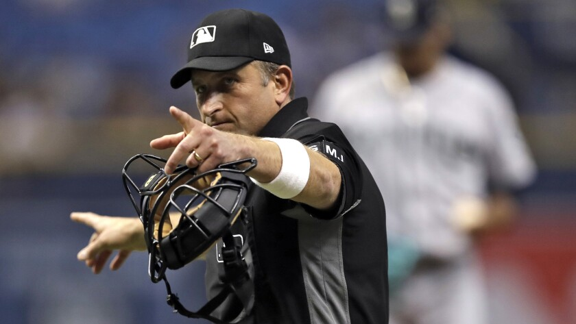 Home-plate umpire Chris Guccione wears a white wristband Saturday during the Rays-Mariners game as a