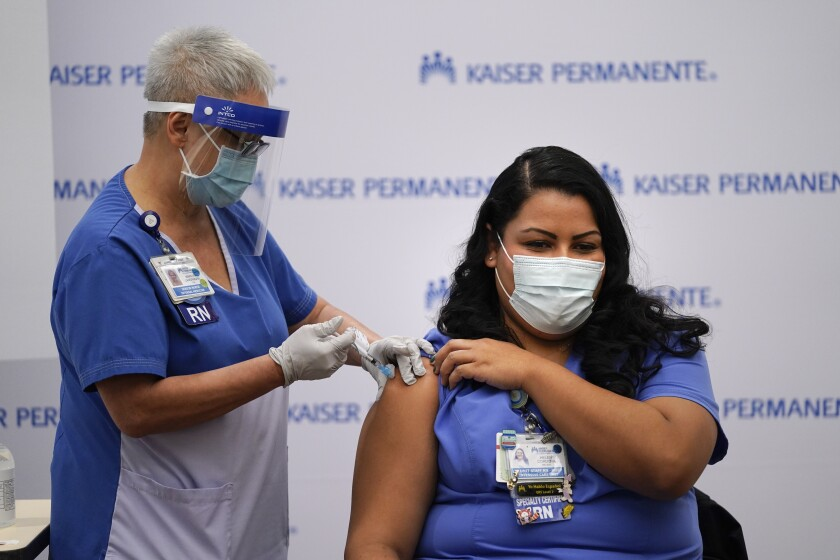 Nurse Helen Cordova receives the Pfizer-BioNTech COVID-19 vaccine at Kaiser Permanente Los Angeles Medical Center on Dec. 14.