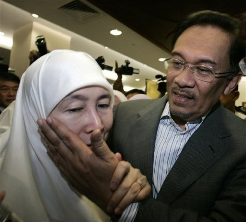 Malaysian opposition leader Anwar Ibrahim, right, comforts his wife Wan Azizah after she was mobbed by media photographers at a courthouse in Kuala Lumpur, Malaysia, Tuesday, Feb. 2, 2010. Anwar arrived in court Tuesday to face a sodomy trial that could transform Malaysia's political landscape. (AP Photo/Lai Seng Sin)