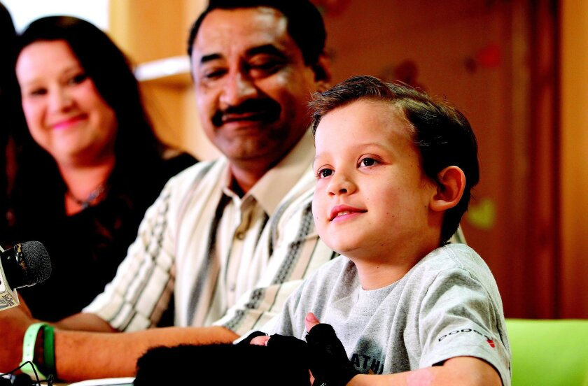 In this file photo from 2012, Luke Acuna, 9, listens to a reporter's question at Rady Children's Hospital with his parents, Anthony and Dawneva Acuna.