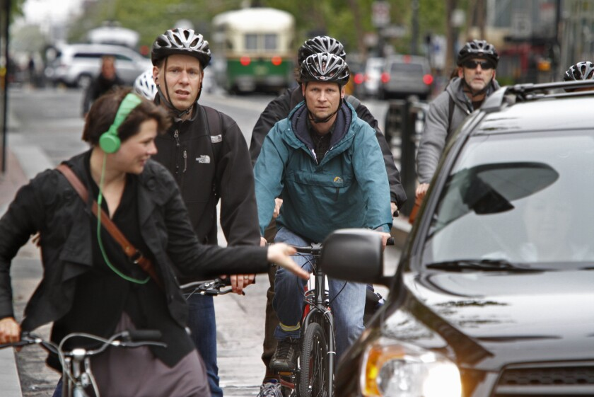 A bicyclist gestures towards a car trying to make a turn through a group during the busy morning commute along Market Street in San Francisco.