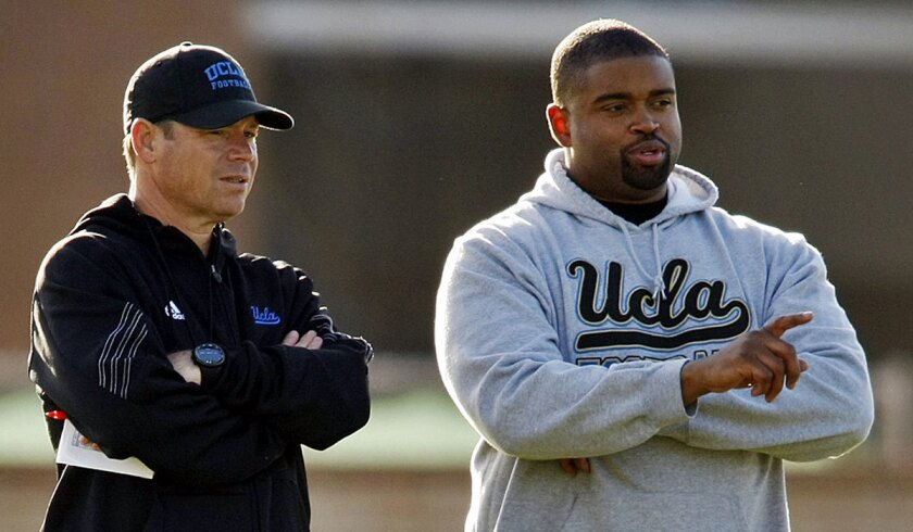 UCLA offensive line coach Adrian Klemm, right, talks to Coach Jim Mora at a practice in 2014.