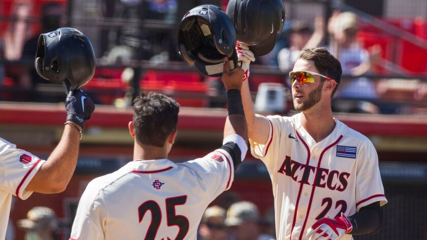 SDSU third baseman David Hensley touches helmets with catcher Dean Nevarez after hitting a two-run homer in the fourth inning.