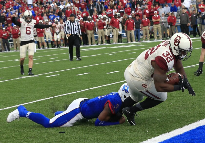 Oklahoma running back Samaje Perine (32) scores a touchdown while tackled by Kansas linebacker Marcquis Roberts (5) during the first half of an NCAA college football game in Lawrence, Kan., Saturday, Oct. 31, 2015. Oklahoma quarterback Baker Mayfield (6) celebrates on the play. (AP Photo/Orlin Wagn