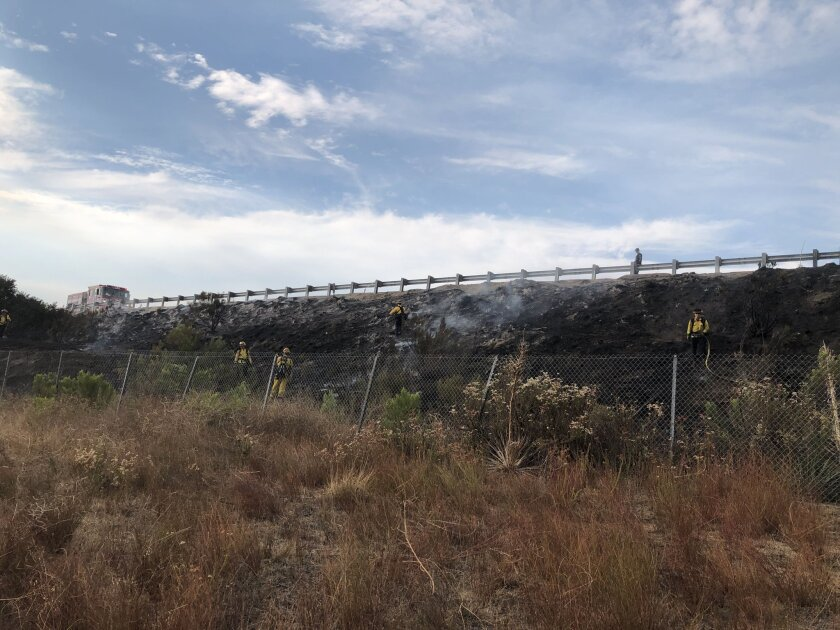 Firefighters extinguish hot spots Thursday afternoon after halting flames that broke out along Interstate 8 in Alpine.