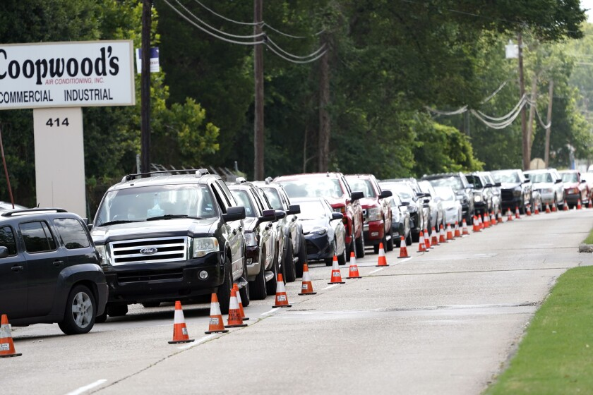 People wait inside their vehicles in line at COVID-19 testing site Wednesday, July 8, 2020, in Houston. (AP Photo/David J. Phillip)